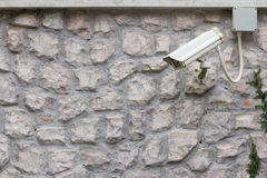 The CCTV Security Camera operating on stone brick wall. Stock Images