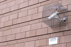 CCTV security camera in operation in cage fixed to wall of workplace office block in city to reduce crime. And create a safer environment Stock Photos