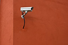 CCTV security camera and red wall. Royalty Free Stock Photo