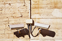 CCTV surveillance cameras on a stone brown wall. Horizontal Shot. CCTV surveillance cameras on a stone brown wall of an office building. Horizontal Shot Stock Photo