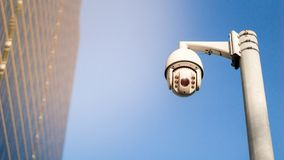 CCTV surveillance security camera on pole in city for safety system area control outdoor with flare light effect and copy space royalty free stock images