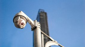 CCTV surveillance security camera on pole in city with tower building background for safety system area control outdoor and copy stock image