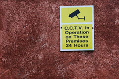 Cctv surveillance sign. Area under cctv surveillance warning sign on wall Stock Photo