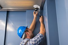 Cctv technician fixing camera. Photo Of Professional Cctv Technician Adjusting Cctv Camera Stock Image