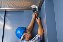Cctv technician fixing camera. Photo Of Professional Cctv Technician Adjusting Cctv Camera Stock Photography