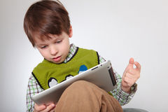 CCute little boy with a tablet pc Stock Photography