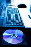 CD的计算机膝上型计算机被开张的盘 库存图片