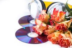 Cd, auscultadores e rosas sobre o branco Imagens de Stock Royalty Free