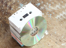 Cd with cassette tape. Cd with bunch of cassette tapes on rusty wooden background royalty free stock photo