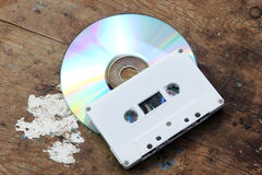 Cd with cassette tape. On rusty wooden background royalty free stock image