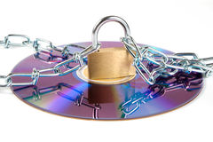 CD with chains. And a padlock. Isolated on a white background stock photo