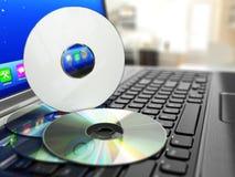 CD de logiciel sur le clavier d'ordinateur portable Disques compacts Photographie stock