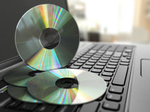 CD de logiciel sur le clavier d'ordinateur portable Disques compacts Photographie stock libre de droits
