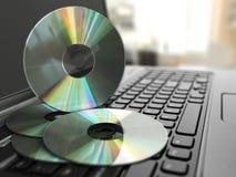 CD del software en el teclado del ordenador portátil diversos colores y tipos Fotografía de archivo libre de regalías