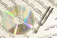 The music concept. CD disc and pitchfork on the notes background. The symbol of classical music and creativity Stock Images