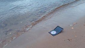 Cd diskett för data i brand på sanden på kusten arkivfilmer