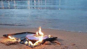 Cd diskett för data i brand på sanden på kusten lager videofilmer