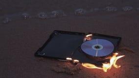 Cd diskett för data i brand på sanden på kusten stock video