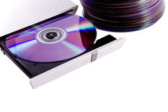 Cd/dvd burner 2. Horizontally oriented cd/dvd burner with a disc inside and stack of a cd's isolated on white. Image with a copy space stock photo