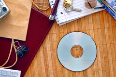 CD or DVD Disc on Messy Desk with Blank Copy Space. CD or DVD disc with empty blank copy space ready for text insert on a messy desk with everyday household stock image