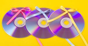 CD/DVD gift. Three CD/DVD gift disks on a yellow background Stock Photos