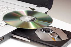 CD/DVD and laptop. CD/DVD dick lying on a laptop with a protruding drive Royalty Free Stock Image