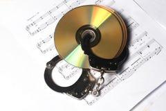 CD of DVD met muzieknoot met handcuff Royalty-vrije Stock Foto's