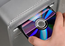 CD or DVD reader. A hand inserting a cd or dvd into a computer royalty free stock photo