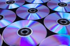 CD/DVDs som ligger på en svart bakgrund med reflexioner av ljus arkivfoton