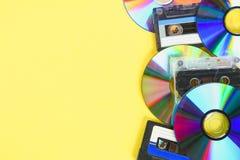 CD dyski i audio kasety na żółtym pastelowym tle minimalista obrazy stock