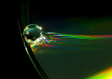 CD edge with water drop. Droplet of water at theedge of a CD Stock Image
