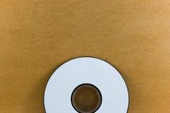 CD en la textura de papel de madera del fondo Imagen de archivo libre de regalías