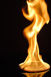 CD in flames. CD or DVD on fire with yellow and orange flames against a black background Stock Images