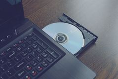 CD inserito in un computer portatile 2 immagini stock