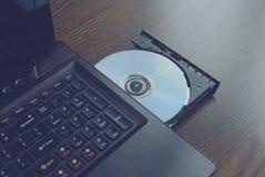 Cd insertado en un ordenador port?til 2 imagenes de archivo