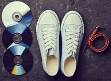CD, leather strap, stylish retro sneakers from 80s. On a black concrete floor. Fashion accessories and digital attributes. Top view stock photos