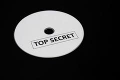 CD mit Aufkleber von streng geheim auf schwarzem Hintergrund Stockfoto