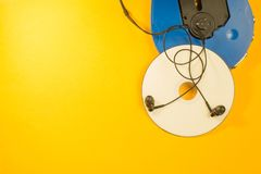 Cd player and compact disc with earphones on yellow background. copy space. Cd player and compact disc with earphones on yellow background stock photos
