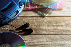CD player with disc and earphones on wooden plank Stock Images