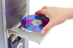 CD-ROM de la mano y del ordenador Foto de archivo libre de regalías