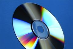 Cd-Rom or DVD rainbow. Cd-Rom reflects colors on a blue background Stock Photos
