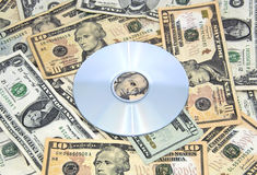 Cd-rom on pile of cash. A cd-rom sits on a pile of US cash Royalty Free Stock Photo