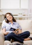 cd som tycker om lyssnande musik för hörlurar till kvinnan Arkivbild