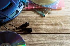 CD speler met schijf en oortelefoons op houten plank Stock Afbeeldingen