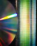 CD Stack. A stack of compact discs with another disc in front. Light reflecting off the disc and colorful light shining through the stack Stock Images
