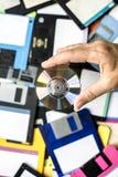 CD van de handholding schijfachtergrond met floppy op de lijst stock afbeelding