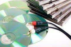 Cdes y casos con el cable audio. Imagenes de archivo