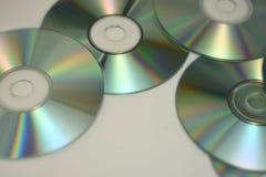 Cdes y DVDs de la música en una pila mientras que brilla fotografía de archivo