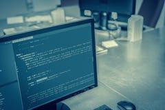 Códigos del sitio web en el monitor de computadora en la oficina Foto de archivo libre de regalías