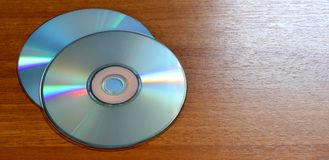 Compact discs on a wooden background. CD on board made of wood royalty free stock photography